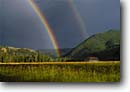 Stock photo. Caption: Rainbow over Rock Creek Valley Rock Creek Granite County Rocky Mountains,  Montana -- united states america summer mountain outdoor recreation rainbows stormy thunderstorm thunderstorms hay hayfield hayfields pasture pastures pastureland pasturelands agriculture agricultural dramactic light fishing stream
