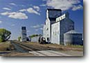 Stock photo. Caption: Railroad tracks and grain elevators Manfred Wells County North Dakota -- destination destinations attractions fall autumn prairies western scenic scenics landscape landscapes sunny blue skies attraction building buildings nostalgia town towns  restored prairie abandoned historic historical silo silos train track transportation