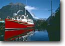 Stock photo. Caption: Ferry at Milford Sound Fiordland National Park South Island New Zealand -- boats boat harbor harbour harbours islands landscape landscapes spring  clear sunny skies ferrys parks reflection  reflections transportation water