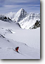 Stock photo. Caption: Downhill skiing the La Cudera Glacier Piz Linard on the skyline The Alps Silvretta, Switzerland,  Europe -- people outdoor recreation backcountry freedom solitude excitement skiers snow mountains expanse vast sports sport cold winter scenic scenics landscape landscapes sunny mountain extreme skier european destination destinations glacier clear alpine swiss