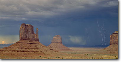 Stock photo. Caption: Thunderstorm over West and East   Mitten Buttes Monument Valley Navajo Tribal Park Colorado Plateau,  Arizona -- canyons parks vista vast spectacular dramatic landscape landscapes tourist destination destinations attraction attractions travel awesome breathtaking erosion time panoramic panoramics panoramas panorama lightning striking strike menacing danger weather
