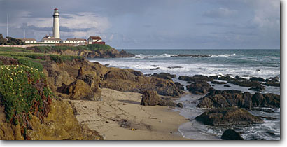 Stock photo. Caption: Pigeon Point Lighthouse San Mateo County coastline California -- panorama panoramas panoramic panoramics landscape landscapes coasts west pacific coastlines summer seascape seascapes ocean oceans scenics scenic lighthouses station light house building tower fence flowers landmarks attractions attractions