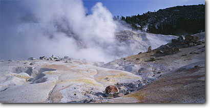 Stock photo. Caption: Hot springs and Bumpass Mountain Bumpass Hell Lassen Volcanic National Park Cascade Range,  California -- volcano volcanoes parks spring united states america tourist hotsprings fumerole area areas geology springs cascades family vacation natural features steamy steam energy volcanic activity desolate panoramic panoramics panoramas clear blue skies sunny view