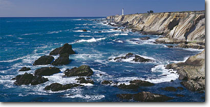 Stock photo. Caption: Sandstone headlands and Point Arena Lighthouse Mendocino County California -- panorama panoramas panoramic panoramics landscape landscapes coasts west pacific coastline coastlines shoreline shore shorelines summer waves surf rocky headlands headland rock cliffs areas rugged bluffs seascape seascapes wave ocean