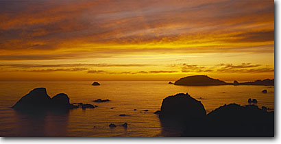Stock photo. Caption: Summer sunset    over Trinidad Head Houda Point and Little River Rocks Humboldt County,  California -- seastacks pacific ocean coast united states seastack west coasts seascape seascapes travel tourist destination destinations golden coastline coastlines break family vacation weekend getaway sunsets panoramic panoramics panoramas panorama landscapes views