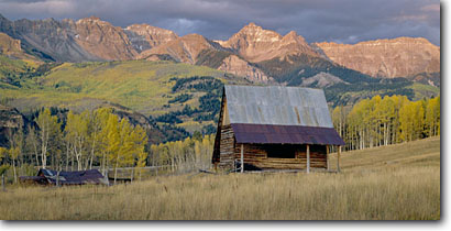 Stock photo. Caption: Old homestead   near Telluride San Juan Mountains Rocky Mountains, Colorado -- panorama panoramas panoramic panoramics landscape landscapes scenic scenics scene barns building buildings fall autumn wooden grasses pastoral rural heritage historic history settlers agriculture roads fence homesteads mesas color colors mountain
