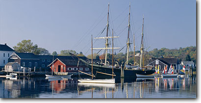 Stock photo. Caption: Early morning light The Museum of America and the Sea Mystic Seaport New London County, Connecticut -- panorama panoramas panoramic panoramics attraction attractions historic historical sunny blue buildings building quaint villages village northern maritime living history museums coastal exhibits seaports fall autumn tall ships ship sailing sailboats