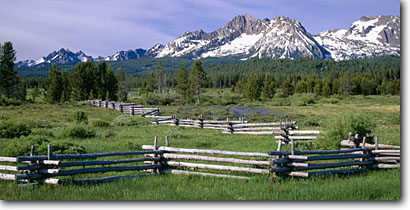 Stock photo. Caption: Pole fence west of Stanley Sawtooth National Recreation Area Sawtooth Mountains Rocky Mountains, Idaho -- panorama panoramic panoramics panoramas landscape landscapes scenic scenics scene attraction attractions destination destinations rockies peaks summer family vacation wild nature areas lakes forests land ranges fences classic areas view views