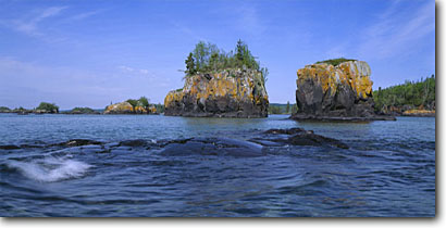 Stock photo. Caption: Lichen covered rocks, Lake Superior Northeast end of Isle Royale Isle Royale National Park Michigan -- parks midwest midwestern landscapes landscape travel lichens wilderness wildernesses great lakes shore shoreline shorelines kayaking areas areas canoeing sunny clear wild scenics scenic panorama panoramas panoramic panoramics