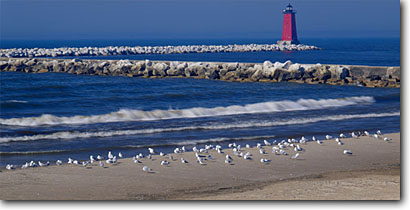 Stock photo. Caption: Manistique East Breakwater Light Manistique Lake Michigan Upper Peninsula,  Michigan -- panorama panoramas panoramic panoramics lighthouses stations landscape landscapes scenic scenics protection buildings building great lakes summer tower sunny clear blue skies shore sandy beach beaches sand lakeshores gulls seagulls birds bird seagull gull
