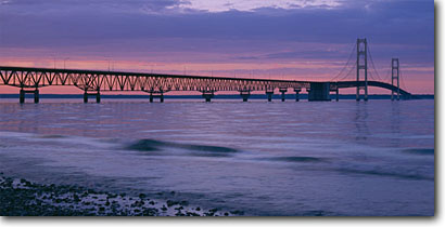 Stock photo. Caption: Mackinac Bridge at sunrise Straits of Mackinac Lake Michigan, St, Ignace Mackinac County, Michigan -- panorama panoramas panoramic panoramics northern landscape landscapes scenic scenics great lakes summer light clouds midwest midwestern sunrises bridges spans famous landmark landmarks shore lakeshore lakeshores water