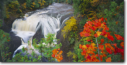 Stock photo. Caption: Red maple and northern white cedar Potawatomi Falls,  Black River Ottawa National Forest Upper Peninsula,  Michigan -- waterfall waterfalls creek creeks stream streams parks fall autumn cloudy united states america midwest midwestern cascade cascades water flowing rivers maples panoramic panoramics panoramas panorama powerful large scenics scenic views view landscapes