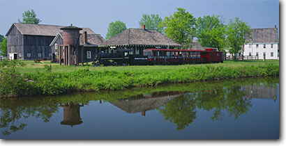 Stock photo. Caption: Erie Canal and Fort Bull Railroad   and Station Erie Canal Village Rome,  New York -- united states barn water tower historic building barns buildings trains canals stations spring tourist attraction attractions historical industry industrial train panoramic panoramics panoramas railroads exhibits exhibit sunny clear blue scenic locomotive