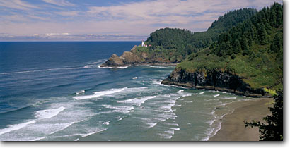 Stock photo. Caption: Heceta Head Lighthouse Devils Elbow State Park Heceta Head State Park Lane County, Oregon -- panorama panoramas panoramic panoramics attraction attractions lighthouses stations landscape landscapes scenic scenics buildings building spring tower waves vast blue skies shore shorelines sandy rock landmarks landmark pacific ocean beach beaches
