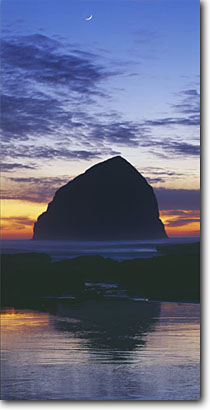 Stock photo. Caption: Haystack Rock   from Cape Kiwanda Cape Kiwanda State Park Tillamook County,  Oregon -- united states seascapes seascape ocean waves spring coast parks pacific west travel tourist destination destinations beaches beach shoreline moon moons beach icon seastack seastacks coastline panoramic panoramics panoramas landmark landscapes landmarks