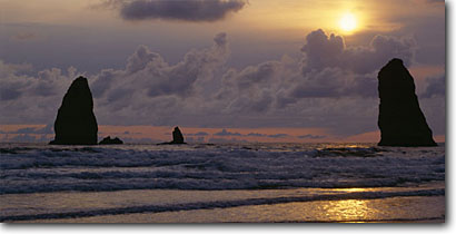 Stock photo. Caption: Cannon Beach at sunset Clatsop County Oregon -- panorama panoramas panoramic panoramics landscape landscapes coast coasts west pacific coastline coastlines shoreline shore shorelines waves surf seascape seascapes wave ocean oceans seastacks seastack landmark landmarks sunsets scenic scenics scene