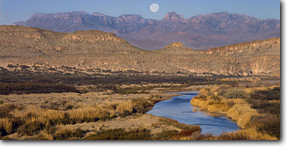 Stock photo. Caption: Moonset at sunrise and Rio Grande River and Chisos Mountains Big Bend National Park Chihuahuan Desert, Texas -- panorama panoramas panoramic panoramics landscape landscapes scenic scenics scene moon moonrises sunrises wetland wetlands clear calm quiet tranquil parks moons rivers view views vista vistas mountain deserts grassland american