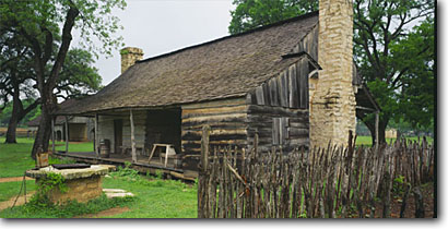 Stock photo. Caption: Sam Ealy Johnson Log House Johnson Settlement,  Johnson City Lyndon B. Johnson  National Historic Park Blanco County, Texas -- historic historical building buildings deserts parks spring decay weathered southwest southwestern country united states tourist travel destination destinations exhibit home preserved cabin cabins panoramic panoramics panoramas pioneer pioneers early