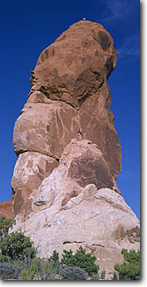 Stock photo. Caption: Climbers on Dark Angel Arches National Park Colorado Plateau Utah -- desert deserts rock canyons country plateaus landscape landscapes tourist travel destination destinations family vacation sandstone slickrock panoramic panoramics panorama climbing sunny clear landmark landmarks sunny clear outdoor recreation people rocks