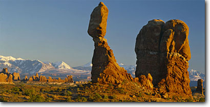 Stock photo. Caption: Balanced Rock   and La Sal Mountains Arches National Park Colorado Plateau, Utah -- parks rock desert deserts buttes slickrock canyon country plateaus survival arid erosion weathered weathering landscape landscapes pristine panoramic panoramics panoramas panorama blue skies clear scenics sunny landmarks snow capped peaks named formations