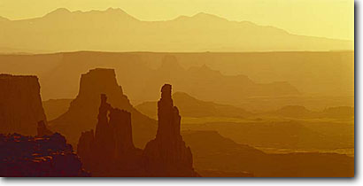 Stock photo. Caption: Washer Woman Arch from Mesa Arch Island in the Sky Canyonlands National Park Colorado Plateau,  Utah -- desert flare sunrises summer deserts rock canyons country parks plateaus spiritual landscape landscapes tourist travel destination destinations arches spire spires butte buttes canyon golden orange light great layers dramatic layered scenics scenic