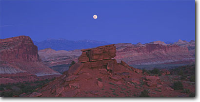 Stock photo. Caption: Waterpocket Fold   and the Henry Mountains Capitol Reef National Park Colorado Plateau,  Utah -- united states america canyon country parks peaks rock peak desert deserts spring landscape landscapes arid  moon moons moonrise moonrises geology geologic panoramic panoramics panoramas panorama clear evening twilight dusk hope life scenic scenics views