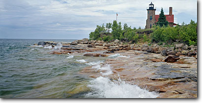 Stock photo. Caption: Sand Island Lighthouse Lake Superior Apostle Islands National Lakeshore Wisconsin -- panorama panoramas panoramic panoramics lighthouses stations landscape landscapes scenic scenics buildings building summer light station house houses shore isolated alone trust faith parks flag flags american great lakes lakeshores parks park attractions