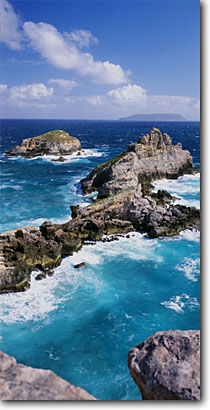 Stock photo. Caption: Pointe des Colibris, La Roche   and La Desirade Pointe des Chateaux Grande Terre Guadeloupe, France -- aqua blue tropical destination destinations vacation vacations tourist travel seascape seascapes island islands exotic warm climate ocean solitude tropical romantic french seastacks surf panoramic panoramics panoramas scenics panorama scenic sunny skies