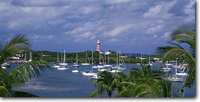 Stock photo. Caption: Elbow Cay Lighthouse and Hope Town   Harbour from Hope Town Harbour Lodge Hope Town,  Elbow Cay Abaco,  Bahamas -- tourist destination destinations travel tropical seascape seascapes aqua lighthouses exotic warm relaxation leisure tourists vacation vacations sailing sail boats boat harbor harbors palms palm mooring panoramic panoramics panoramas tropics sailboats view