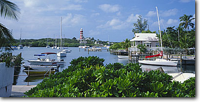 Stock photo. Caption: Elbow Cay Lighthouse and Hope Town Harbour from Back Street Hope Town, Elbow Cay  Abaco, Bahamas -- tourist destination destinations travel tropical seascape seascapes  lighthouses exotic warm relaxation leisure tourists vacation vacations sailing sail boats boat harbor harbors palms palm mooring panoramic panoramics panoramas sailboats harbours scenics