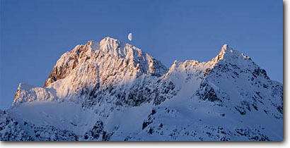 Stock photo. Caption: Moon rise over the Piz Buin Ochsentaler Glacier Silvretta Austria, Europe -- outdoor recreation backcountry freedom solitude dramatic awesome snow mountains expanse cold winter scenic scenics landscape landscapes traverse sunny mountain extreme destination destinations clear alpine backcountry european moonrise moons moonrises