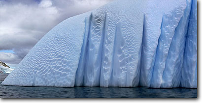 Stock photo. Caption: Sculpted blue icebergs Gerlache Straits Antarctic Peninsula Southern Ocean,  Antarctica -- Keywords: iceberg icebergs severe extreme weather climate global warming  aquatic flightless south pole continent southern glacial penguin snow habitat birds bird ethereal breathtaking sculpture patterns panoramic panoramics panoramas